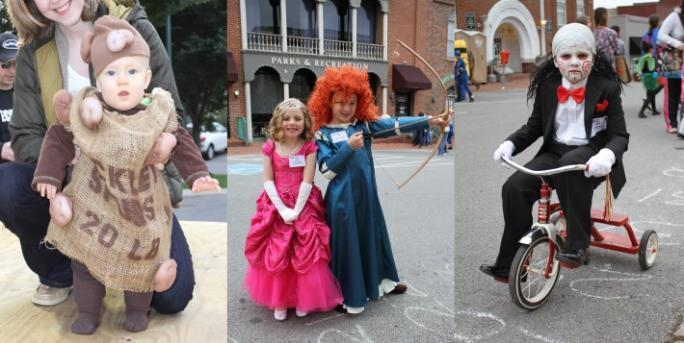 Child dressed up as sack of potatoes, beside two girls dressed as Sleeping Beauty and Merida, boy on tricycle